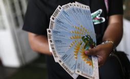 A Colombian fan displays his FIFA 2014 World Cup tickets for the match between Colombia and Greece, in Rio de Janeiro April 18, 2014. REUTERS/Ricardo Moraes