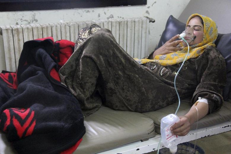 A woman, affected by what activists say was a gas attack, breathes through an oxygen mask inside a field hospital in Kfar Zeita village in the central province of Hama April 12, 2014. REUTERS/Stringer