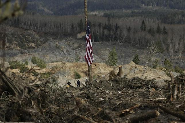A flag flies at half staff as workers look out over the mud and debris as search work continues from a massive mudslide that struck Oso near Darrington, Washington April 2, 2014. REUTERS/Jason Redmond