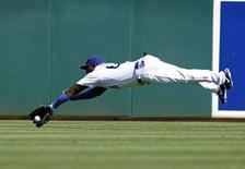 Los Angeles Dodgers center fielder Yasiel Puig attempts to make a diving catch of a fly ball off the bat of Cincinnati Reds' Brandon Phillips during the fifth inning of their MLB Cactus League spring training baseball game in Glendale, Arizona, March 22, 2013. REUTERS/Ralph D. Freso