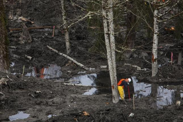 A rescue worker takes a break while working in a debris field left by a mudslide in Oso, Washington April 3, 2014. REUTERS/Max Whittaker