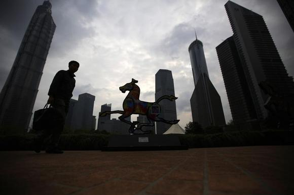 A man walks next to a horse statue in a park at Pudong financial district in Shanghai April 2, 2014. REUTERS/Carlos Barria