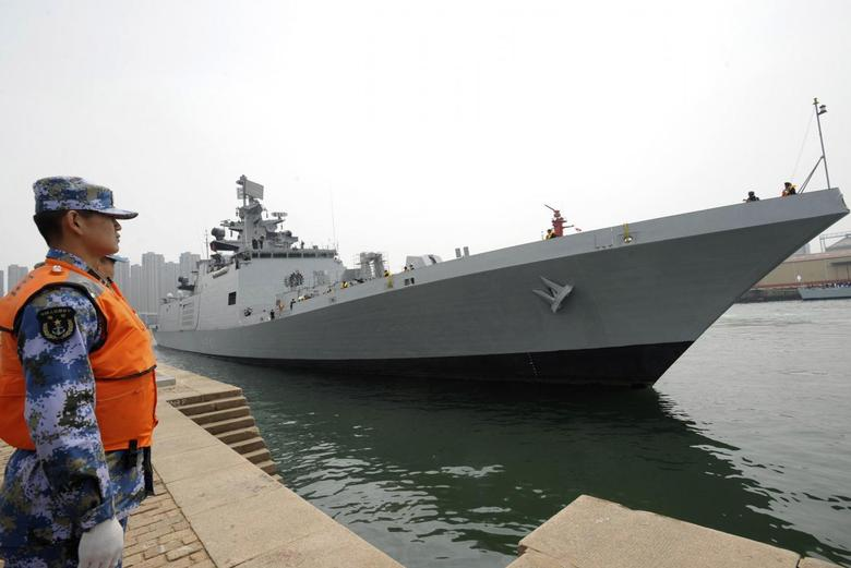 A Chinese navy personnel (L) stands guard as Indian naval frigate INS SHIVALIK is seen docked at a military port after its arrival before a maritime drill during the Western Pacific Naval Symposium in Qingdao, Shandong province, April 20, 2014. REUTERS/Stringer