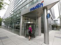 A woman walks into the Nexen building in downtown Calgary, Alberta, July 23, 2012. REUTERS/Todd Korol