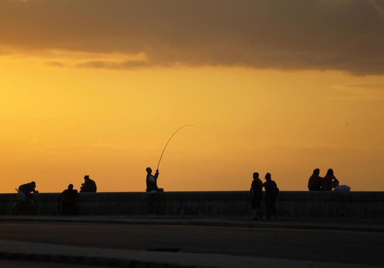 A man pulls at his fishing rod as the sun sets on Havana's seafront boulevard El Malecon December 3, 2013. REUTERS/Desmond Boylan