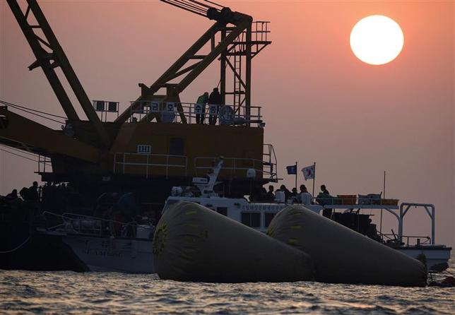 South Korean rescue workers operate near floats, where the capsized ferry Sewol sank, during the search and rescue operation in the sea off Jindo during sunset April 22, 2014. REUTERS/Issei Kato