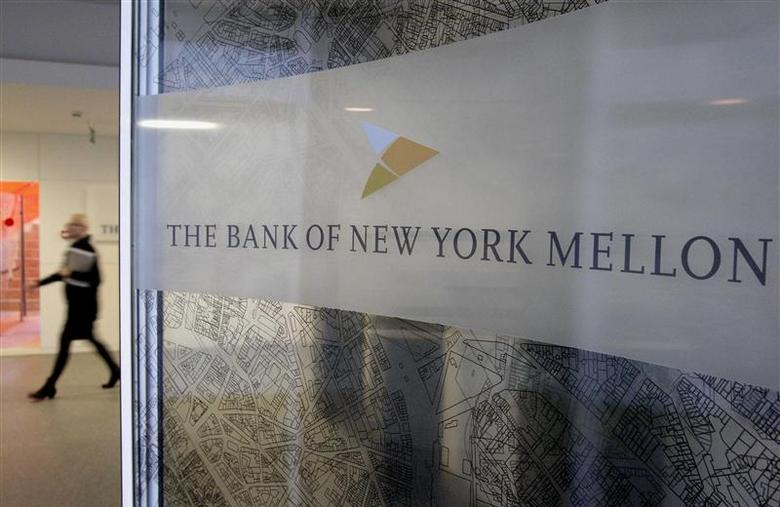 A woman walks past a logo at the office of the Bank of New York Mellon in Brussels in this file photo taken February 25, 2010. REUTERS/Sebastien Pirlet/Files
