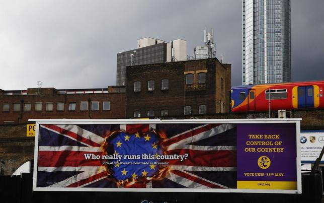 A train passes above a United Kingdom Independence Party (UKIP) European elections campaign poster in Vauxhall, central London April 22, 2014. REUTERS/Luke MacGregor
