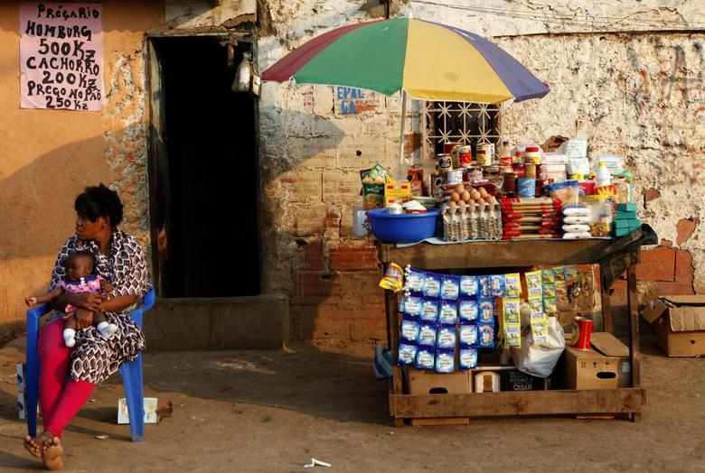 A woman holding a child sits in front of her stall in Sambizanga informal settlement, outside the capital Luanda in this August 28, 2012 file photo. REUTERS/Siphiwe Sibeko/Files