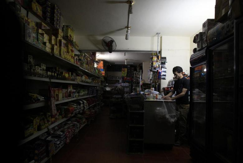 A supermarket seller stands near an emergency light during power outage at his shop in Cairo April 16, 2014. REUTERS/Amr Abdallah Dalsh