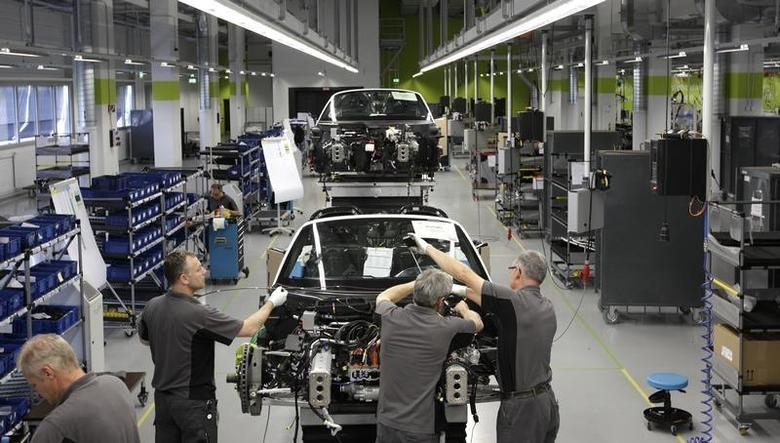Electricians assemble a new Porsche 918-Spyder sports car at the production line of the German car manufacturer's plant in Stuttgart-Zuffenhausen July 2, 2013. REUTERS/Michaela Rehle