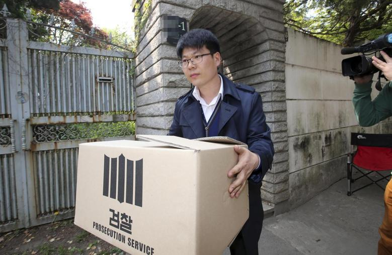An official from the Incheon District Prosecutors' office carries a box during a raid of the home of Yoo Byung-un, in Seoul April 23, 2014. REUTERS/Yonhap