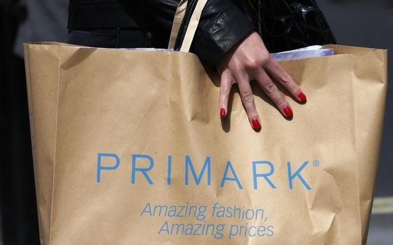 A shopper passes demonstrators outside clothing retailer Primark in London April 27, 2013.REUTERS/Suzanne Plunkett