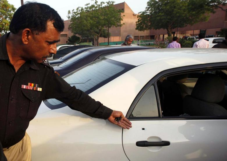 A policeman shows the media a bullet hole in the door of a car which belongs to journalist Hamid Mir, at a local hospital in Karachi April 19, 2014. REUTERS/Athar Hussain