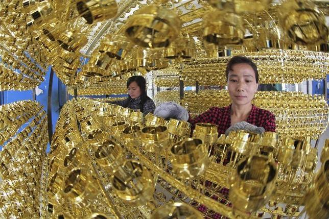 Employees work on the production line of a wine bottle cap factory in Ganyu county, Jiangsu province May 6, 2013. REUTERS/China Daily