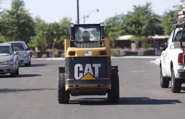 A worker drives a Caterpillar tractor near a construction site in Gilbert, Arizona October 20, 2009.REUTERS/Joshua Lott