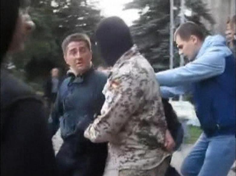 Horlivka city deputy Volodymyr Rybak (L) is manhandled by several men, among them a masked man in camouflage, outside a city hall building in Horlivka in this still image taken from video filmed by gorlovka.ua on April 17, 2014 and provided to Reuters on April 23, 2014. REUTERS/Gorlovka.ua via Reuters TV