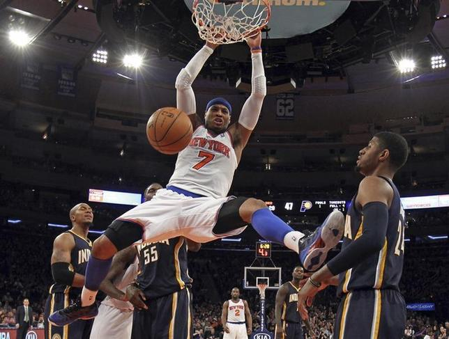 New York Knicks forward Carmelo Anthony slam dunks the ball in front of Indiana Pacers forward Paul George (R) in the second half of their NBA basketball game at Madison Square Garden in New York, April 14, 2013. REUTERS/Adam Hunger