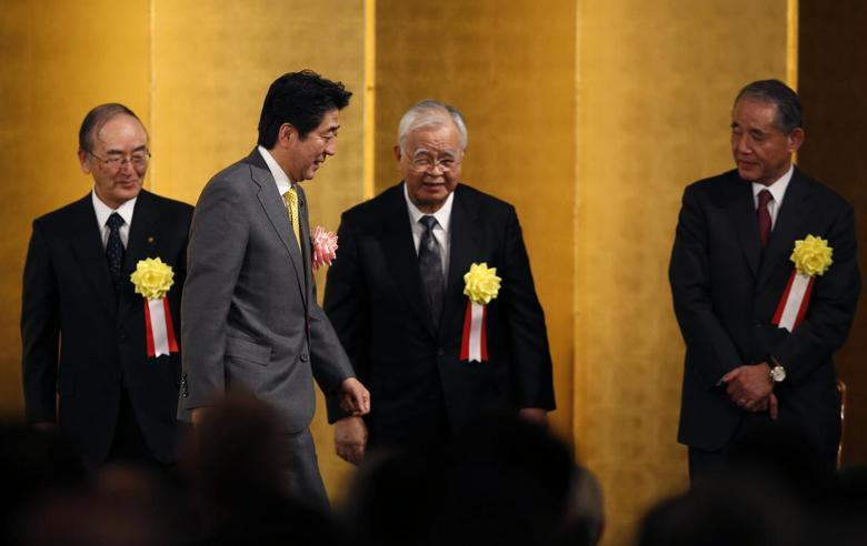 Japan's Prime Minister Shinzo Abe (2nd L) walks past Japan Chamber of Commerce and Industry Chairman Akio Mimura (L), Japan Business Federation (Keidanren) Chairman Hiromasa Yonekura (2nd R) and Japan Association of Corporate Executives Chairman Yasuchika Hasegawa after making a speech during the business lobbies' New Year party in Tokyo January 7, 2014. EUTERS/Toru Hanai
