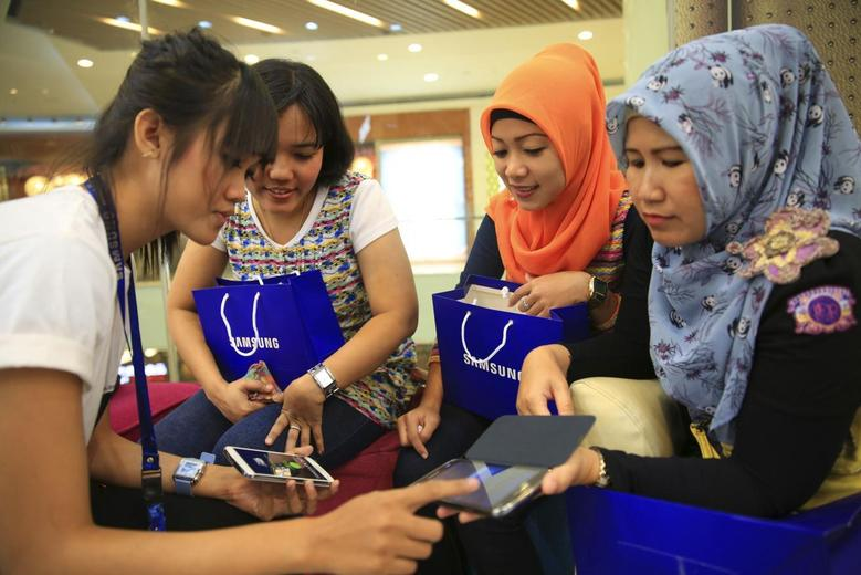 Women listen as a Samsung employee provides instructions on using their new Galaxy smartphones in Jakarta, April 11, 2014. REUTERS/Beawiharta