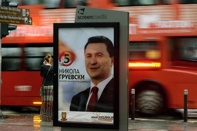 People walk past campaign posters of Macedonian ruling party VMRO-DPMNE leader and current Prime Miniester Nikola Gruevski in Skopje April 23, 2014. REUTERS/Ognen Teofilovski