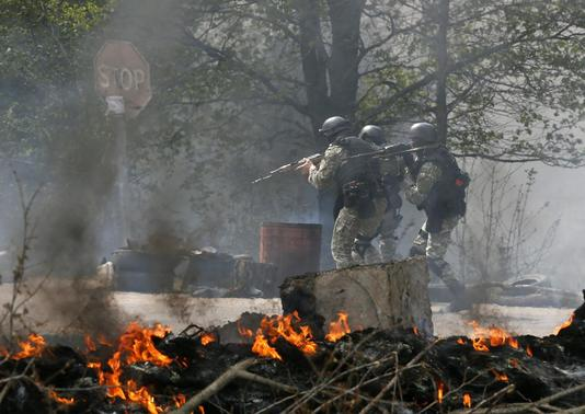Ukrainian security force officers walk past a checkpoint set on fire and left by pro-Russian separatists near Slaviansk April 24, 2014. REUTERS/Gleb Garanich