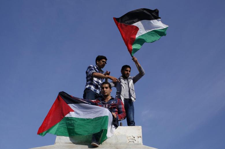 Palestinians hold national flags as they celebrate after an announcement of a reconciliation agreement in Gaza City April 23, 2014. REUTERS/Ibraheem Abu Mustafa