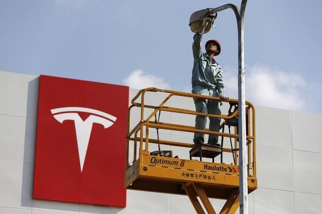 A labourer repairs a street lamp next to a logo of Tesla Motors in front of a new showroom of the company in Shanghai, April 22, 2014. REUTERS/Stringer