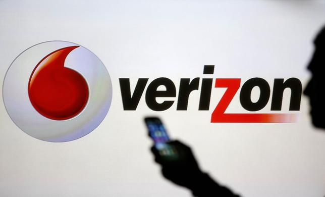 A man is silhouetted against a video screen with Vodafone and Verizon logos as he poses with a Samsung Galaxy S3 in this photo illustration taken in the central Bosnian town of Zenica, September 3, 2013. REUTERS/Dado Ruvic