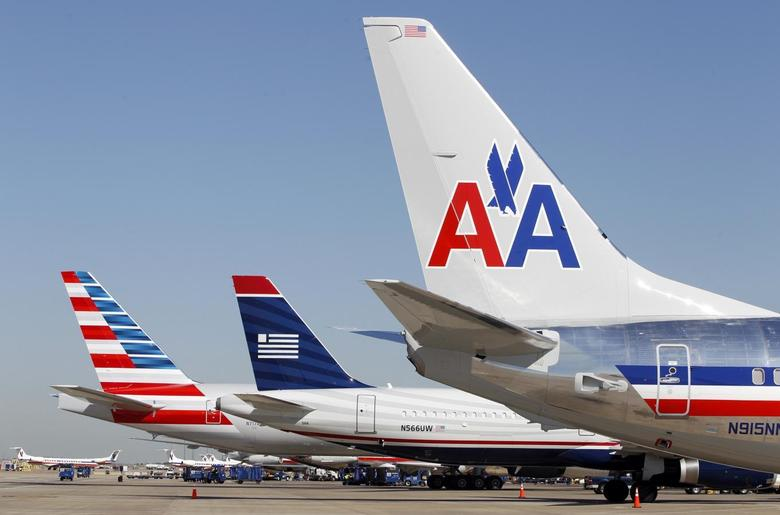 The tail sections of a newly designed American Airlines aircraft (L), a US Airways aircraft (C) and a traditional American Airlines aircraft are lined up at Dallas-Ft Worth International Airport February 14, 2013. REUTERS/Mike Stone