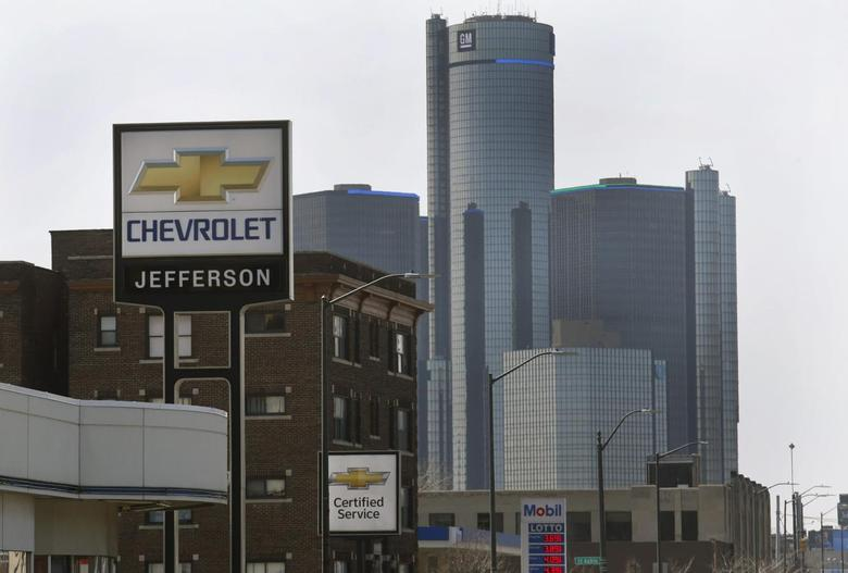 The sign to a Chevrolet automobile dealership is seen down the street from General Motors World Headquarters on Jefferson Avenue in Detroit, Michigan April 2, 2014. REUTERS/Rebecca Cook