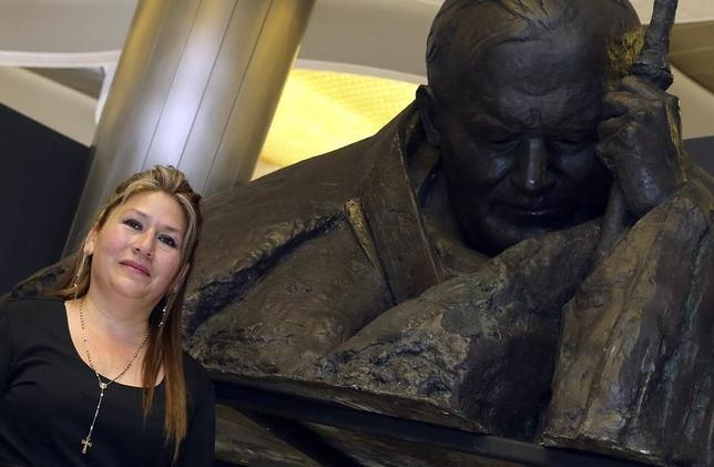 Costa Rican woman Floribeth Mora Diaz poses near a statue of John Paul II after she speaking to the media about the miracle that set Pope John Paul II onto the road of sainthood at the Vatican April 24, 2014. REUTERS/Alessandro Bianchi