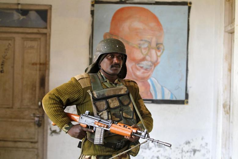 An Indian security personnel stands guard in front of a portrait of Mahatma Gandhi at a polling station in Merhama, south of Srinagar April 24, 2014. REUTERS/Danish Ismail