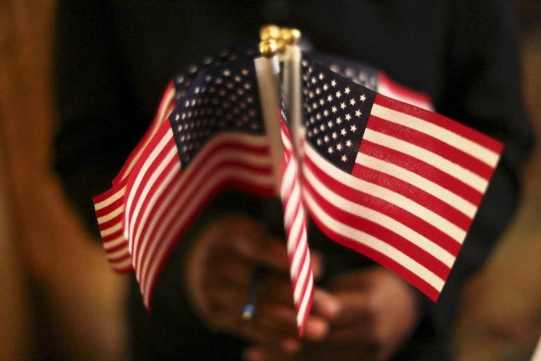 A woman holds a cluster of U.S. flags during a U.S. Citizenship and Immigration Services naturalization ceremony in Oakland, California August 13, 2013. REUTERS/Robert Galbraith