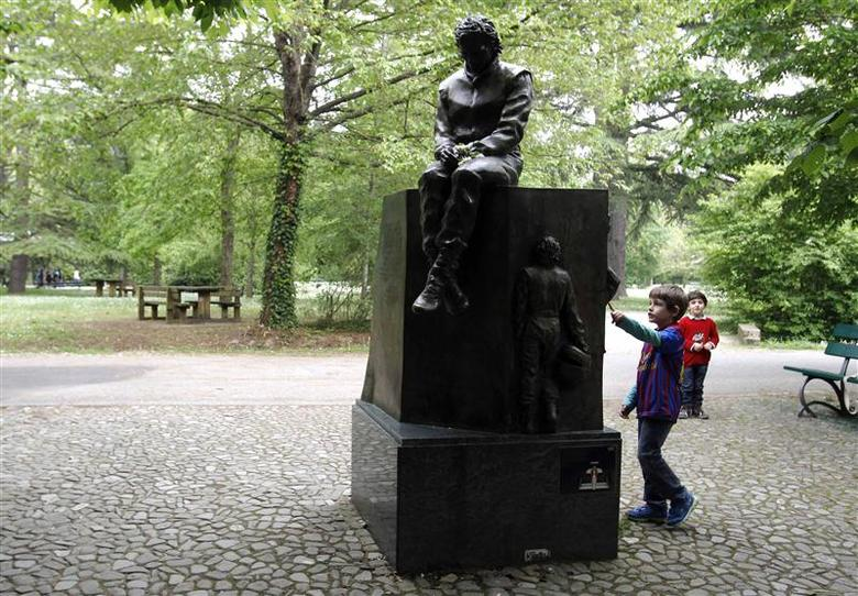 Children play next to the memorial statue of Formula One Brazilian driver Ayrton Senna in the park inside the race track at Imola April 22, 2014. REUTERS/Alessandro Garofalo