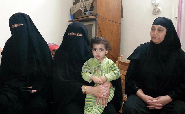 The wife (L) and other family members of Fahmy Abdel Raouf, who was killed with his 13-year-old son in a gun battle with security forces, sit in their flat in the Matariya area of Cairo April 13, 2014. Picture taken April 13. REUTERS/Stringer
