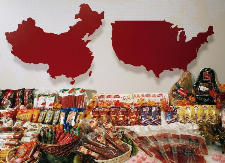Some of the products of WH Group are displayed in front of maps of China (L) and the United States at a news conference on the company's IPO in Hong Kong April 14, 2014. REUTERS/Bobby Yip