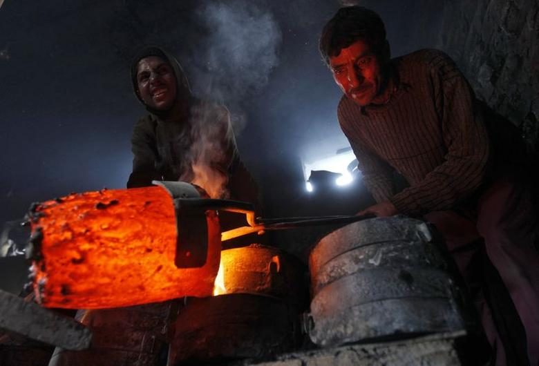 Workers pour melted copper in a mould to make utensils and accessories inside a workshop in Srinagar March 27, 2014. REUTERS/Danish Ismail/Files