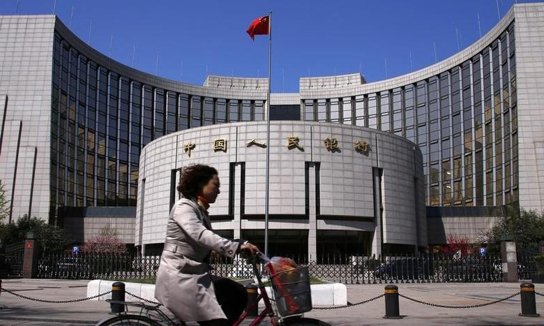 A woman rides past the headquarters of the People's Bank of China (PBOC), the central bank, in Beijing, April 3, 2014.REUTERS/Petar Kujundzic