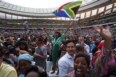 "A woman flies a South African flag during the ""Nelson Mandela: A Life Celebrated"" memorial service at Cape Town Stadium December 11, 2013. REUTERS/Mark Wessels"