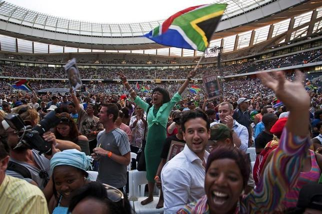 A woman flies a South African flag during the ''Nelson Mandela: A Life Celebrated'' memorial service at Cape Town Stadium December 11, 2013. REUTERS/Mark Wessels