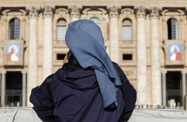 A nun prays in front of tapestry featuring Pope John Paul II (L) and Pope John XXIII in St. Peter's square at the Vatican, April 25, 2014. REUTERS/Stefano Rellandini