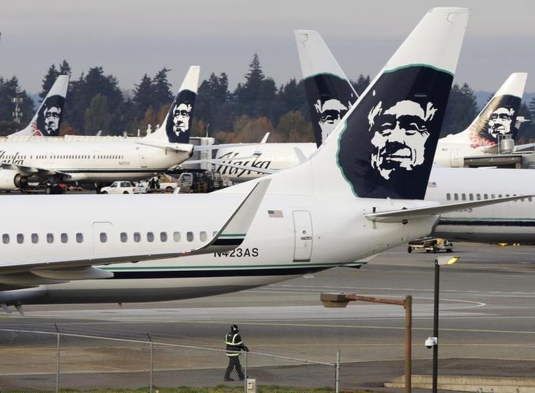 A ground crew member walks near Alaska Airlines planes parked at Seattle-Tacoma International Airport in SeaTac, Washington October 30, 2013. REUTERS/Jason Redmond