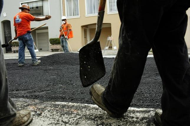 Workers spread asphalt on a street in the Cow Hollow neighborhood in San Francisco, California June 2, 2010. REUTERS/Robert Galbraith