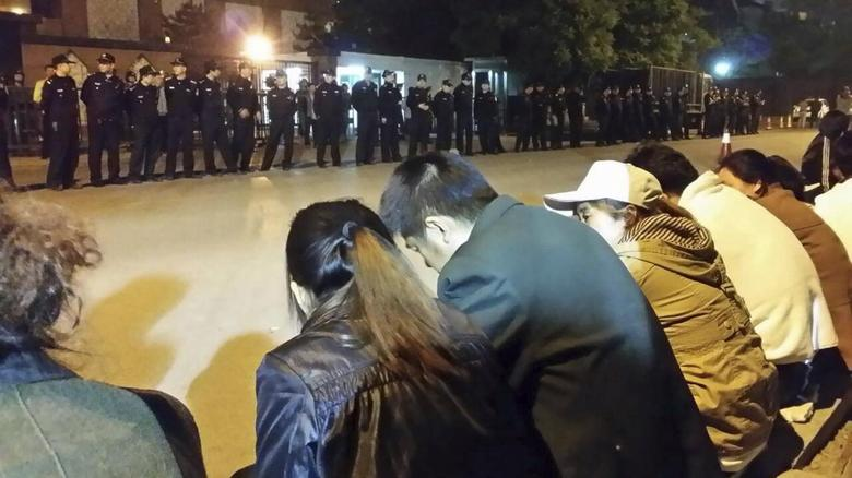 Family members (front) of passengers aboard missing Malaysia Airlines flight MH370 gather for a sit-in protest as security personnel stand guard outside the Malaysian embassy in Beijing, early April 25, 2014. REUTERS/Courtesy of family members/Handout via Reuters