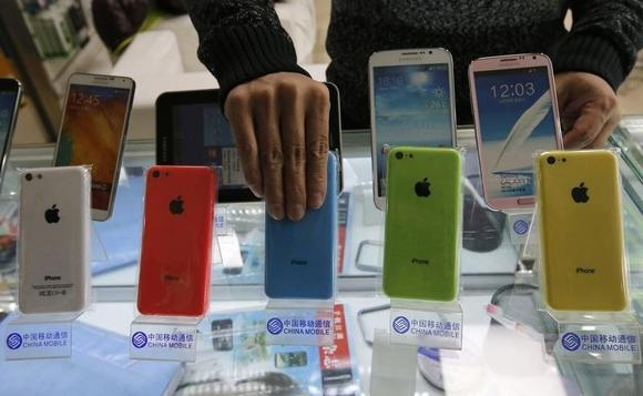 A clerk arranges Apple's iPhone 5C phones on racks bearing the logo of  China Mobile, at a mobile phone shop in Beijing December 23, 2013. REUTERS/Kim Kyung-Hoon/Files