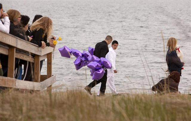 Students arrive at the beach for a vigil in honor of slain student Maren Sanchez wearing their prom clothes carrying balloons in Milford, Connecticut April 25, 2014. REUTERS/Michelle McLoughlin