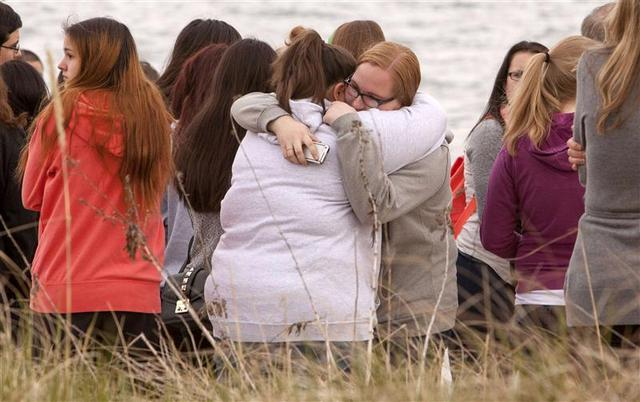 People gather on the beach for a vigil in honor of slain student Maren Sanchez in Milford, Connecticut April 25, 2014. REUTERS/Michelle McLoughlin