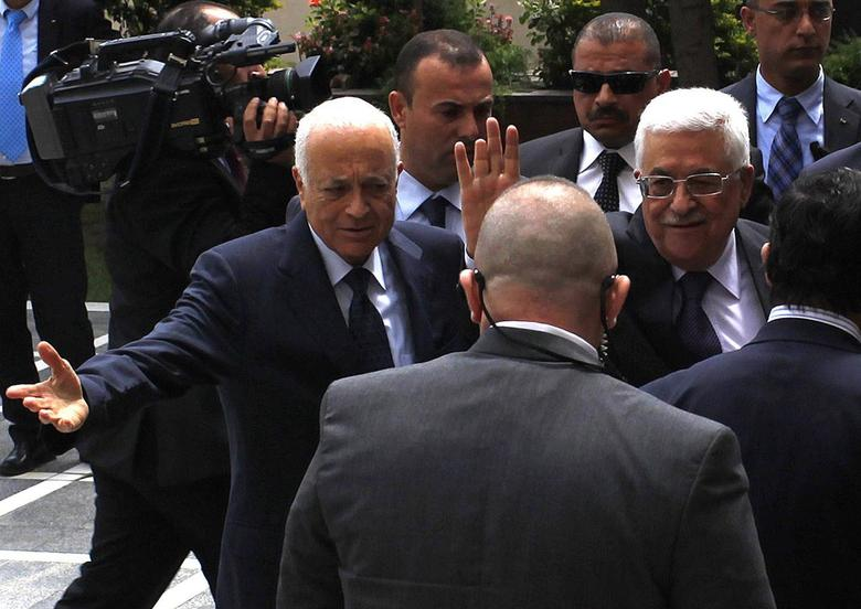 Arab League Chief Nabil al-Arabi (L) greets Palestinian President Mahmoud Abbas, who waves to the media, before attending an Arab Foreign Ministers' meeting at the Arab League headquarters in Cairo April 9, 2014. REUTERS/Asmaa Waguih