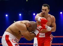 World heavyweight boxing champions Vladimir Klitschko of Ukraine lands a punch on Australian challenger Alex Leapai (L) during their WBO heavyweight title fight in Oberhausen April 26, 2014. REUTERS/Kai Pfaffenbach